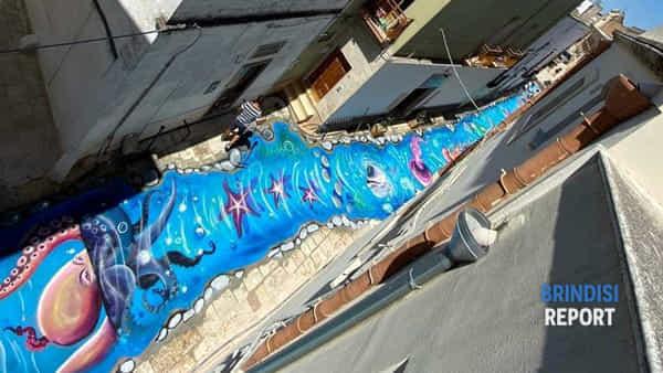 Un vicolo che fa sognare: pesci, meduse e stelle marine tra le case