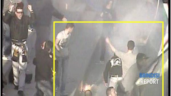 Un tifoso con la felpa nera cerca di allontanare il fumogeno dallo striscione